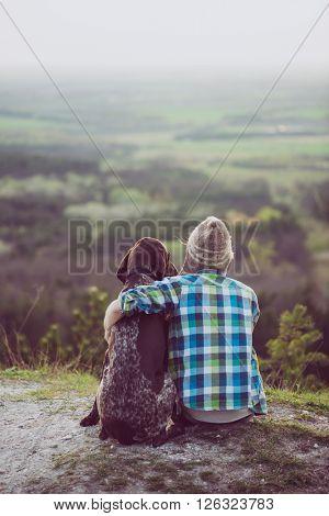 Woman and her dog posing outdoor. Young explorer woman loving and hugging tightly her German pointer dog and watching landscape.