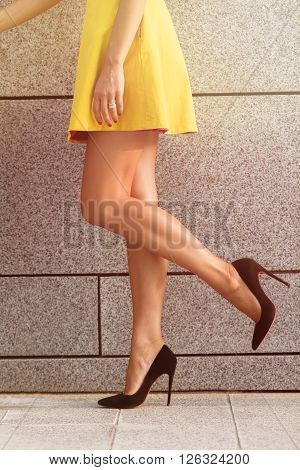 Close-up image of woman's legs in profile. Slim and slender legs on black high heels isolated on brick wall background. Toned image.