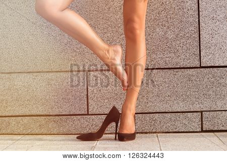 Low view of woman's legs isolated on brick wall backround. Lady on high heels posing for photographer. She put off one of her heel and put one leg after another. Toned image.