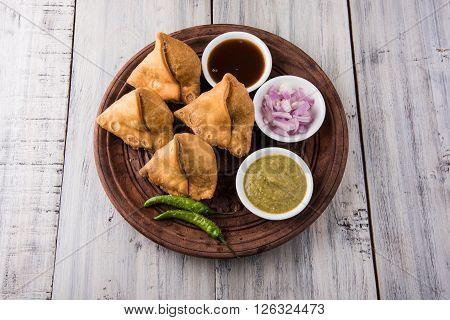 Veg potato Samosa with sauces, Homemade Fried Indian Samosa with Mint Chutney Sauce, famous indian tea time snack
