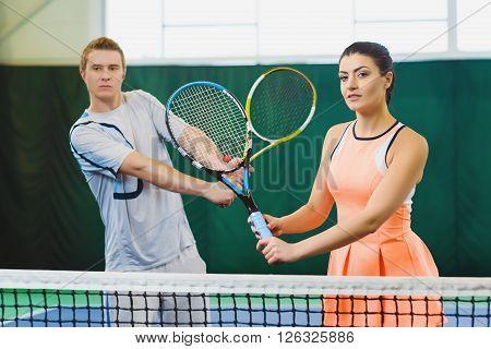 Mixed Doubles player hitting tennis ball, partner standing near net.
