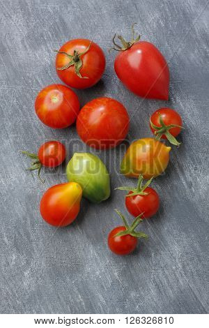 Variety of tomato fruits over painted textile background. Two fruits unripe. Overhead view.