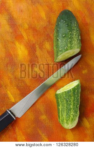 Halved cucumber and knife over painted textile background. Overhead view.