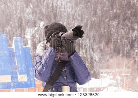 A Young Girl Takes Pictures Winter Mountain Landscape In A Snow Storm On A Slr Camera With Telephoto