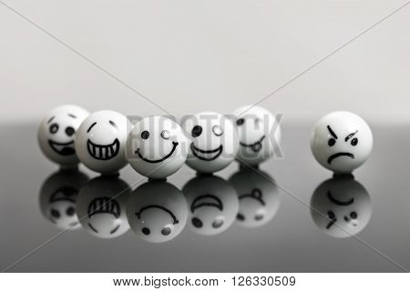 white marbles with faces on a black stone with reflections. concept teamwork and success with one misfit