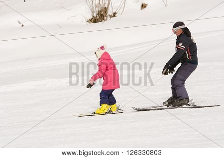 Dombay, Russia - February 7, 2015: A Man Learns To Ski Teenage Girl On A Snow-covered Slope Ski Reso
