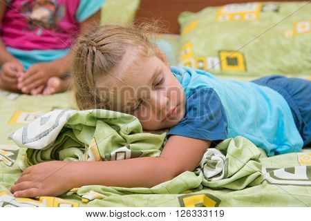 The Little Girl Sleeps On A Double Bed Crumpling Under The Blanket