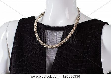 Black top with simple necklace. Plain bijouterie necklace on mannequin. Dark top with net inset. Exclusive element of woman's apparel.