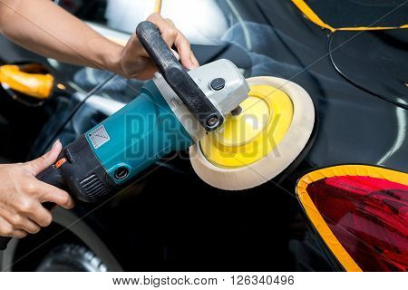 Car detailing series : Worker polishing black car