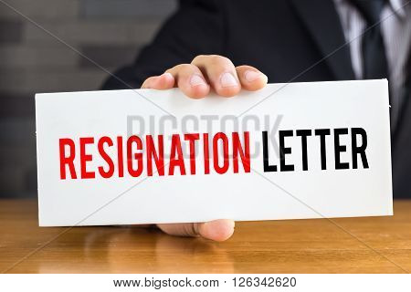 Resignation letter message on white card and hold by businessman