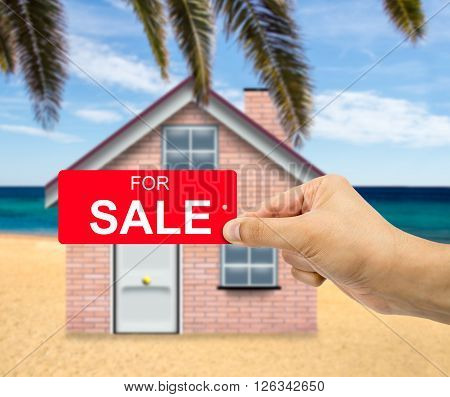 Man holding card home For sale sign red label with percent sign in hand with sale concept and beach house background