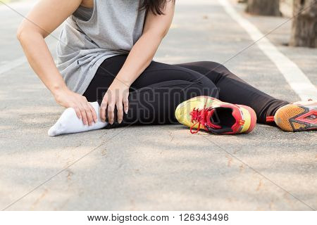 Sports injury. Woman with pain in ankle while jogging in park