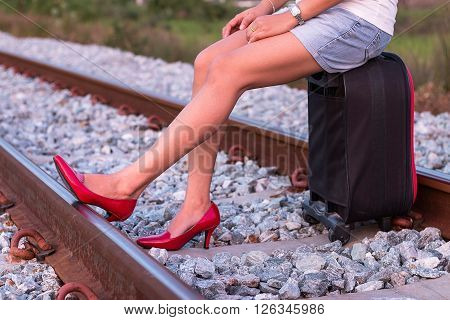 Woman legs in red high heel shoes and sitting on suitcase in railway