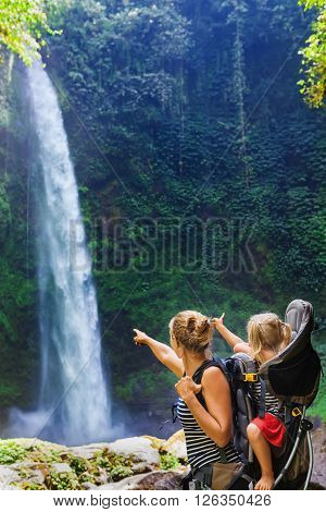 Young happy woman hold little traveller in back baby carrier explore jungle waterfall in rainforest. Hiking activity adventure and fun with child on family summer vacation travel weekend nature tour