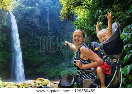 In waterfall pool young happy mother hold little traveller on back - baby girl in carrying backpack enjoying travel adventure Hiking activity with child on family summer vacation weekend nature tour