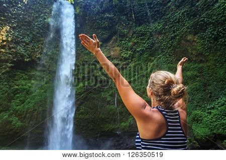 Young happy woman in tourist camp spreading hands enjoying nature and fresh water waterfall traveling in Bali rainforest. Nature day tour hiking activity adventure and fun on family summer vacation.