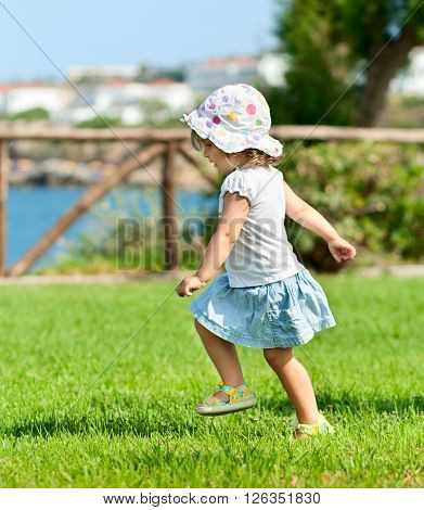Little baby girl running outdors, summer time