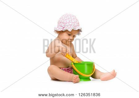 Cute little child in swimming pants and sunhat, sitting with toys for sand isolated over white