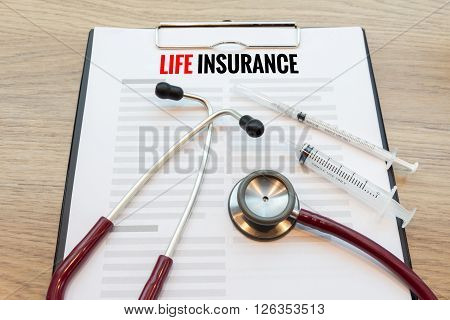 Life insurance form with stethoscope and hypodermic syringe.