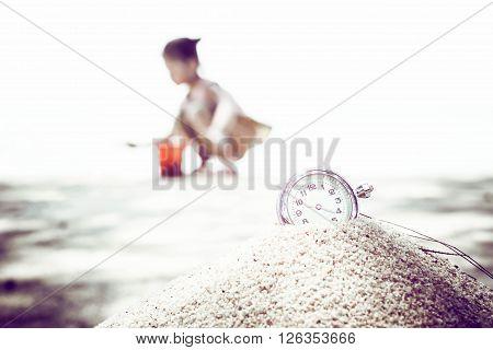 vintage pocket watch on sand, holiday summertime.