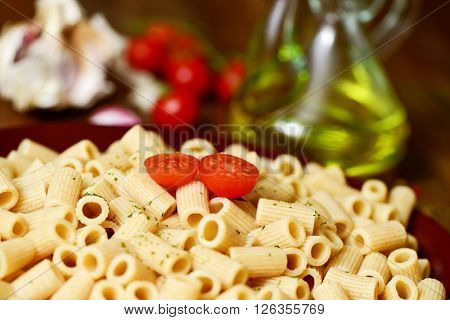 closeup of a plate with cooked penne rigate on a table with garlic cloves, tomatoes and a glass cruet with olive oil in the background