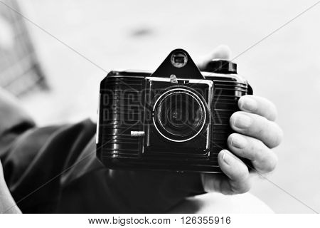 closeup of an old caucasian man with an old camera in his hand, in black and white