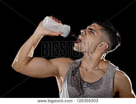 close up portrait of young athletic sport man thirsty drinking water holding the bottle pouring the fluid on his sweaty face refreshing and recovering after hard training workout in hydration concept poster