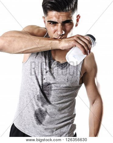 close up portrait of young athletic sport man thirsty holding bottle of water with sweaty face and wet singlet after refreshing and recovering after hard training workout in hydration concept