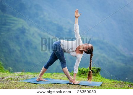 Woman doing Ashtanga Vinyasa yoga asana Parivrtta trikonasana - revolved triangle pose outdoors