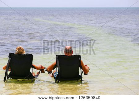 BIG PINE KEY, USA - MAY 10, 2015: A couple sitting on camping chairs with drinks in the shallow water near the beach of Little Duck Key in Florida.