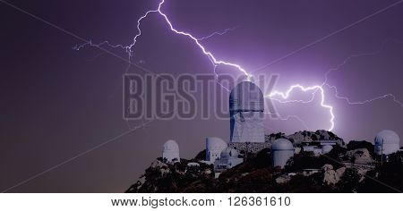 A Bolt of Lightning Strikes Over a Mountaintop Observatory at Night