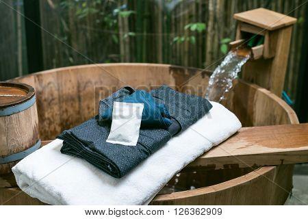 Onsen series : wooden bathtub with blue yukata and white towel
