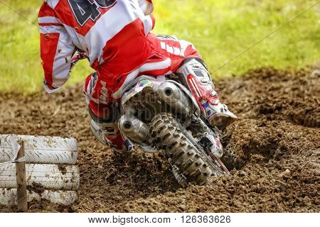 Rear view of motocross bike rider who drifts around a white painted tire stack. The rear wheel is digging deep in the sand and throws dirt in the air.