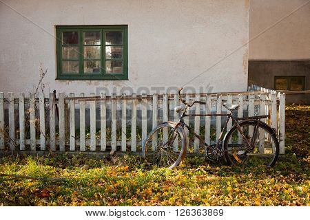 Abandoned vintage bicycle leaning against a fence in autumn