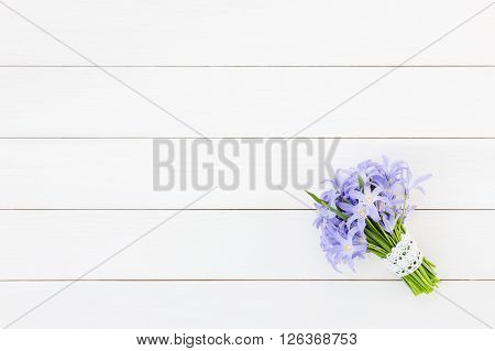 Bouquet Of Spring Flowers Decorated With Lace On White Wooden Background. Top View, Copy Space. Chio