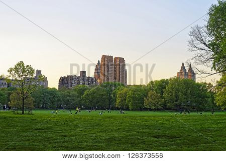 View on Uptown Manhattan skyline in Central Park West. On Upper West Side in New York USA. People nearby