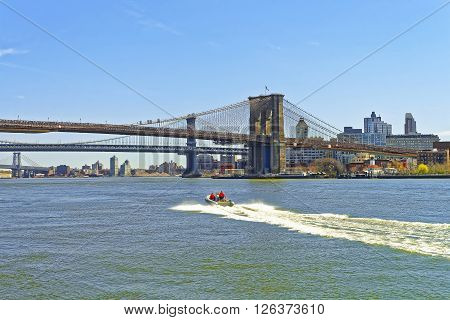 View from Ferry on Brooklyn bridge and Manhattan bridge above East River. Bridges connect Lower Manhattan with Brooklyn Heights of New York USA. Boat near the Brooklyn Bridge. Tourists on board