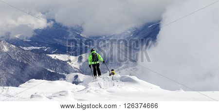 Freeriders On Off-piste Slope And Mountains In Mist