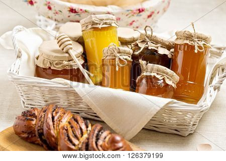 Honey in jars and rolls. Selective focus.