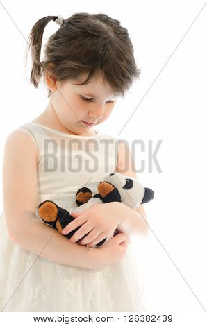 Sweet little girl playing with her teddy bear bedding him isolated on white bakground
