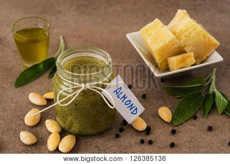 Pesto of almonds and pecorino cheese in a glass jar on a wooden table ** Note: Visible grain at 100%, best at smaller sizes