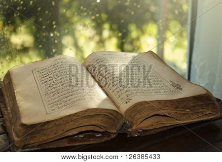 Old holy Quran book at bright window sun light