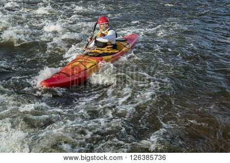 senior whitewater kayaker paddling upstream the river rapid
