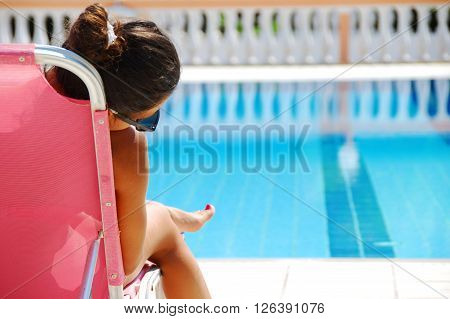 teenage girl sitting by the blue clear transparent swimming pool ** Note: Soft Focus at 100%, best at smaller sizes