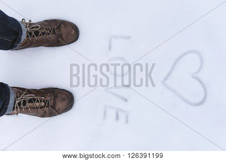Men's Shoe Close Up View With Love Simbol Wrtien On The Snow