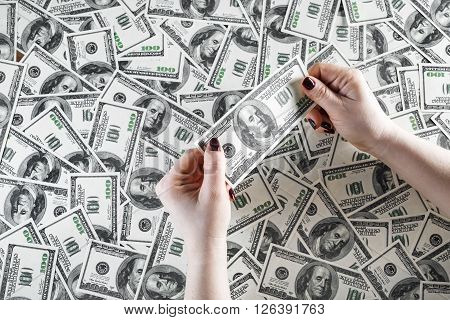 Check the authenticity of money. One hundred dollar bill in female hands on a background of money. Checking money. Cash in hands. Fake money in hands. Money in female hands.