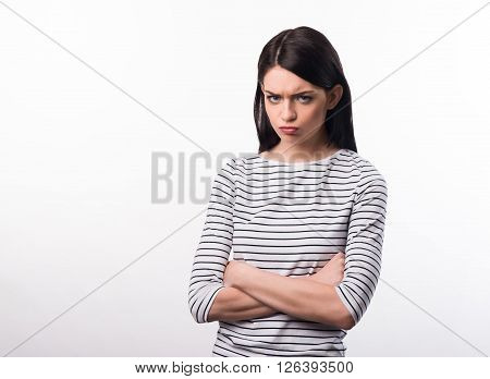 Out of temper. Gloomy  cheerless girl folding her hands and expressing dissatisfaction while standing isolated on white background