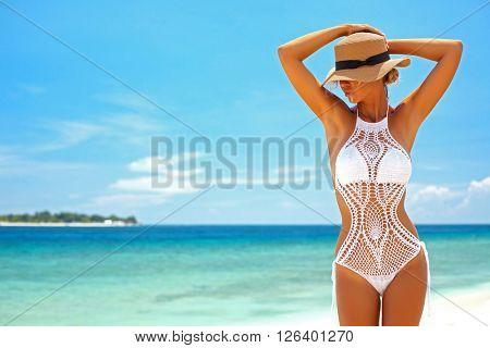 Beautiful woman wearing crochet bikini posing over the sea view, beach lifestyle