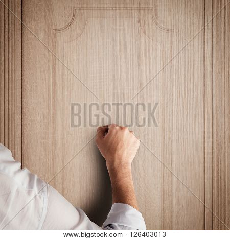 Business man knocks to a wooden door