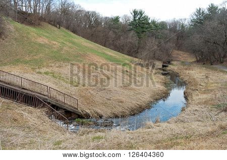 battle creek regional park scenic with hillside and stream flowing through spillway along trail